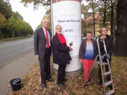 Überklebten Tabakreklame in Potsdam: Lothar Binding (MdB, SPD), Johannes Spatz (Forum Rauchfrei), Kathrin Vogler (MdB, DIE LINKE) und Giovanni Schulze (v.l.n.r); Foto via Forum Rauchfrei