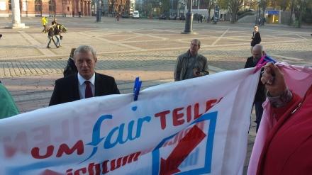 Stadtkämmerer trifft vor dem Rathaus auf UMfairTEILEN-Aufforderungen.