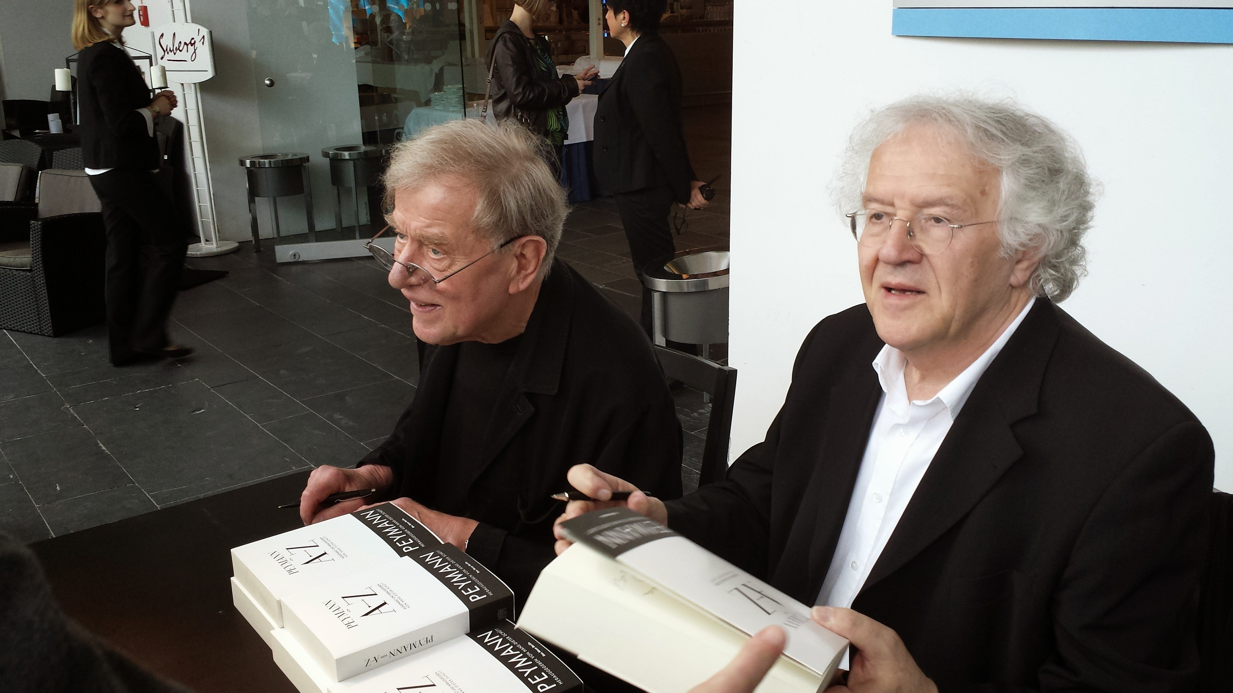 Claus Peymann (links) und Hermann Beil (rechts) beim Signieren eines Buches.