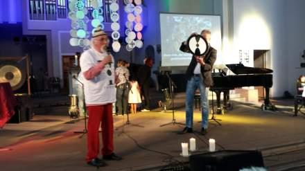 """Leo Lebendig (links) erklärt das Symbol """"Zwei Menschen in einem Kopf"""" (rechts in den  Händen von Pastor Friedrich Laker."""