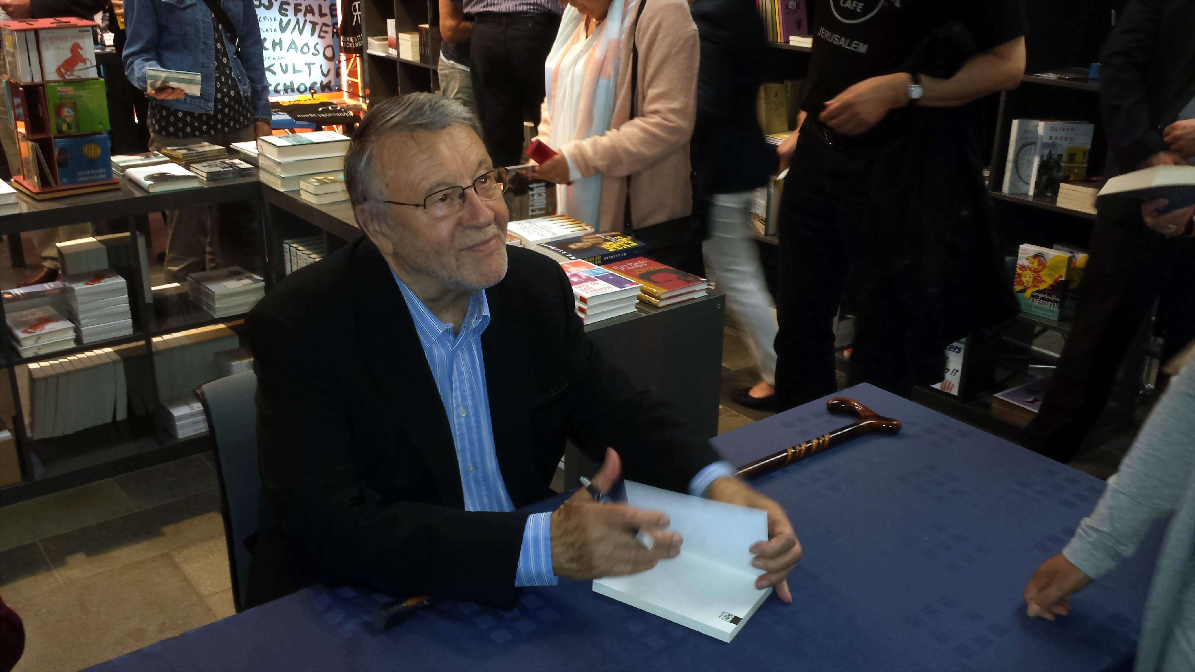 Günter Lamprecht signiert das Exemplar eines seiner Bücher.